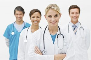 Beautiful young doctor standing with hands folded and assistant doctors in background